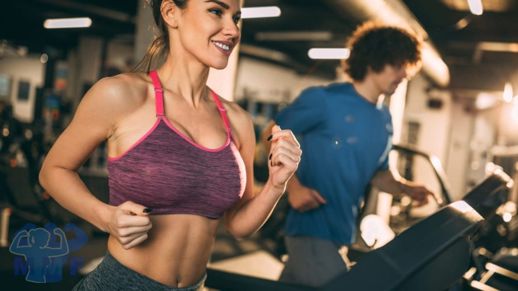 Beautiful fit woman in the foreground and man in the background on treadmills discussing the importance of aerobic exercise.