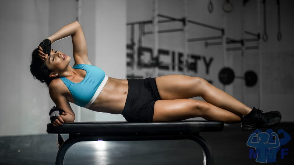 Women lying on a gym bench enjoying the afterburn effect HIIT workout results.