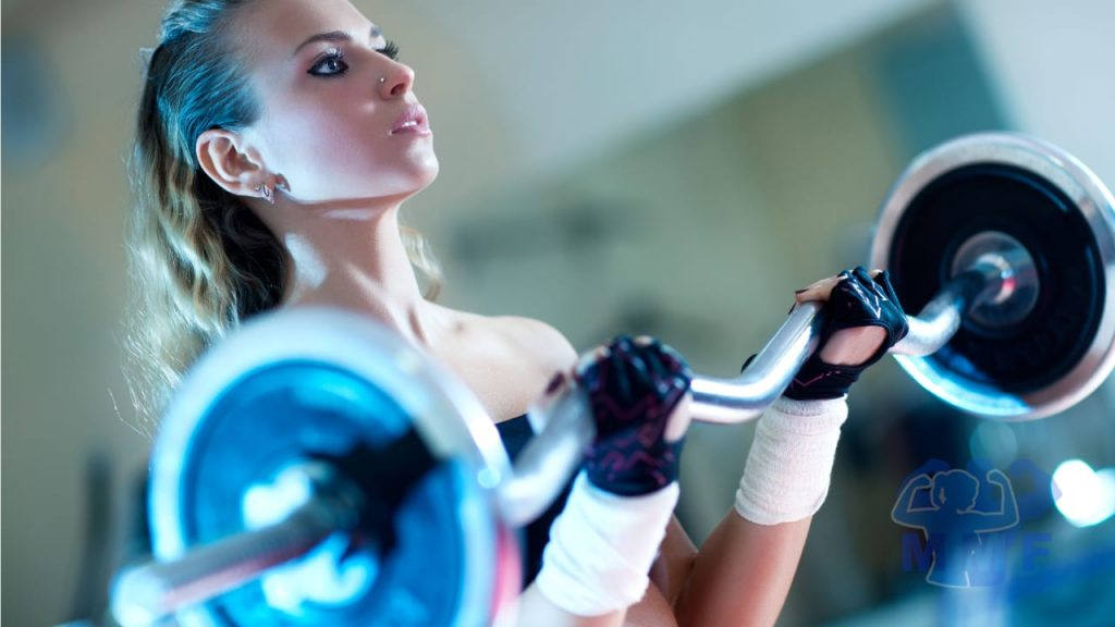 Fit woman performing ez barbell curls with lifting gloves and nose piercing.