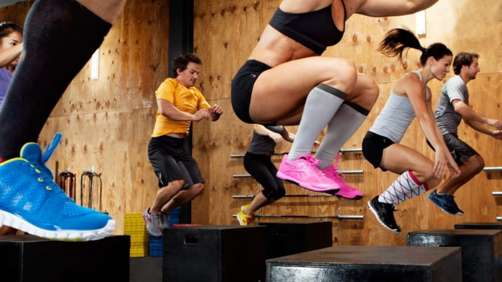Fit Men and Women Doing Box Jumps In A Workout Class Getting An Edge In Sports With Plyometrics Benefits.