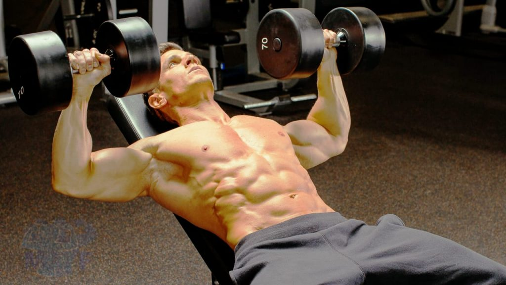 Buff shirtless man performing incline dumbbell bench press in a gym.