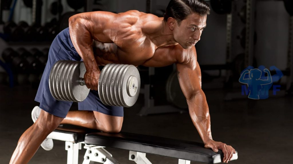 Buff man performing single-arm dumbbell row on bench at gym.
