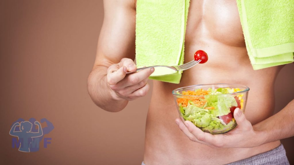Strong fit shirtless man eating a salad with a green towel around his neck, with a cherry tomato on his fork wonder is calorie restriction and longevity true.