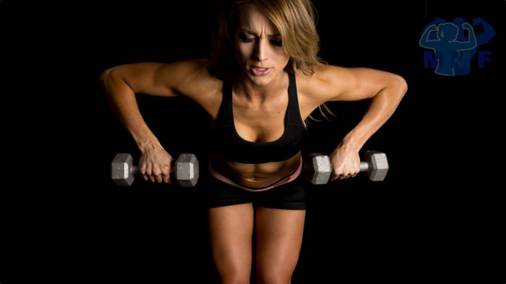 Fit woman performing dumbbell bent over row in black workout clothes on in dark black background.