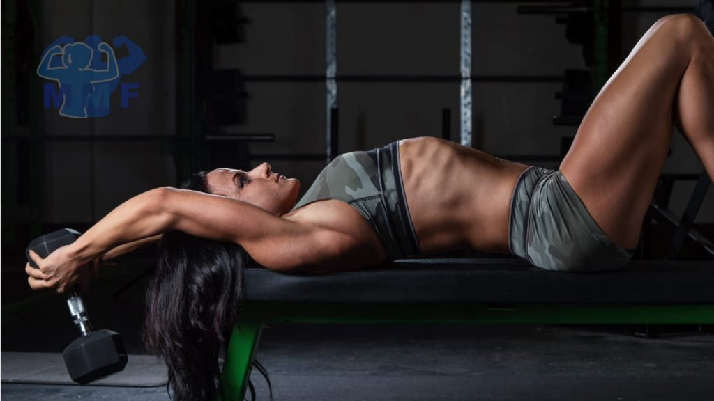 Fit woman performing dumbbell pullovers on a bench.