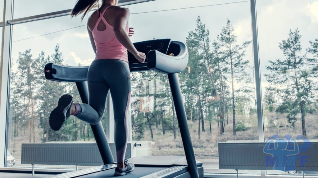 Fit lean woman running on a Treadmill looking outside. Performing HIIT to get lean fast.