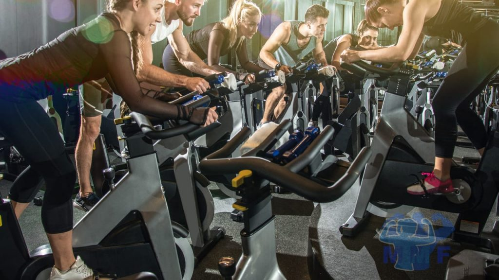 Group performing high-intensity interval training in a cycling spin class.