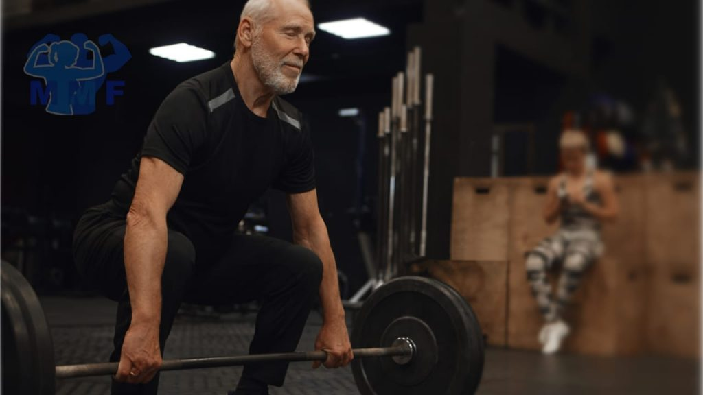 Man in 60s doing deadlifts and build muscle after 50. With a woman in the background looking at her phone.