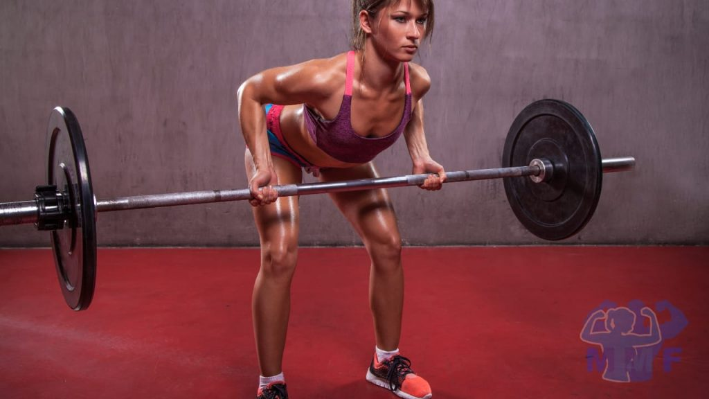 Fit woman performing underhand barbell bent over rows.