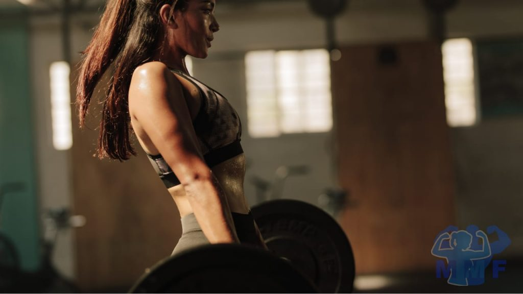 Fit beautiful woman weight lifting for weight loss with deadlifts.
