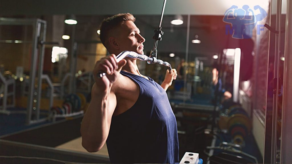 Fit man performing lat pulldowns in a gym.