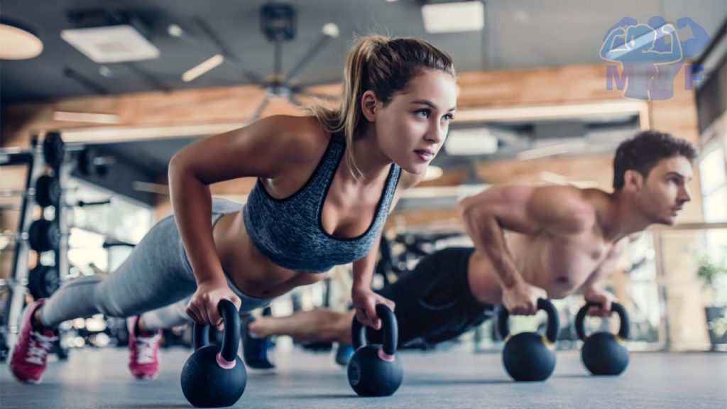 Fit woman and man doing push ups on kettlebells at a gym.