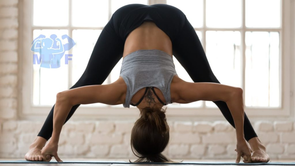 Fit, flexible woman performing prasarita padottanasana