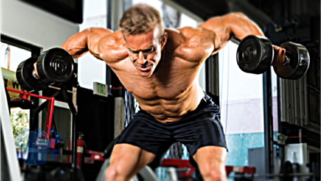 Muscular man without a shirt performing dumbbell rear lateral raises in a gym.