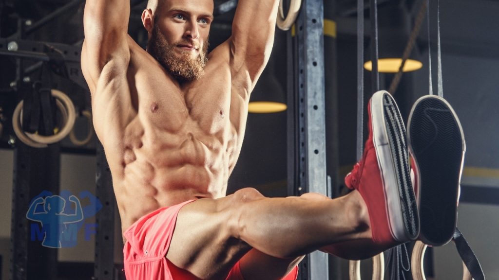 Strong man performing hanging leg raises as part of a six pack workout.