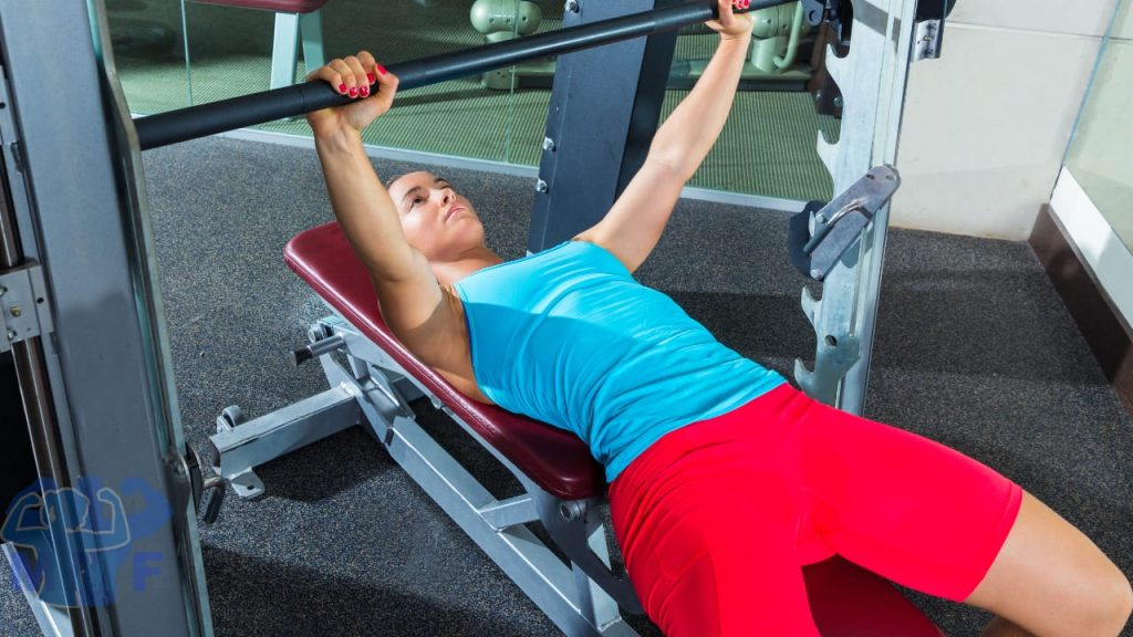 Young fit woman performing Smith Machine Bench Press in a blue top and red shorts.