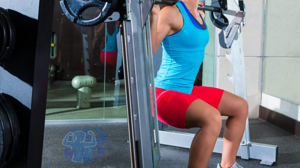 Fit woman performing smith machine squats at the gym. MuscleMagFitness.com logo.