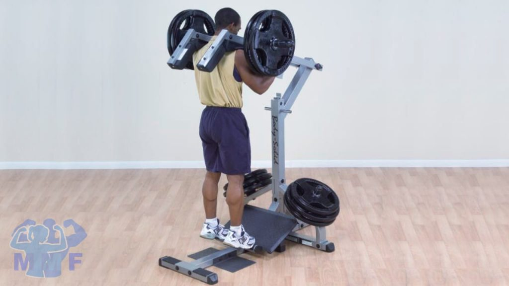 Man on a standing calf raise machine with white background.