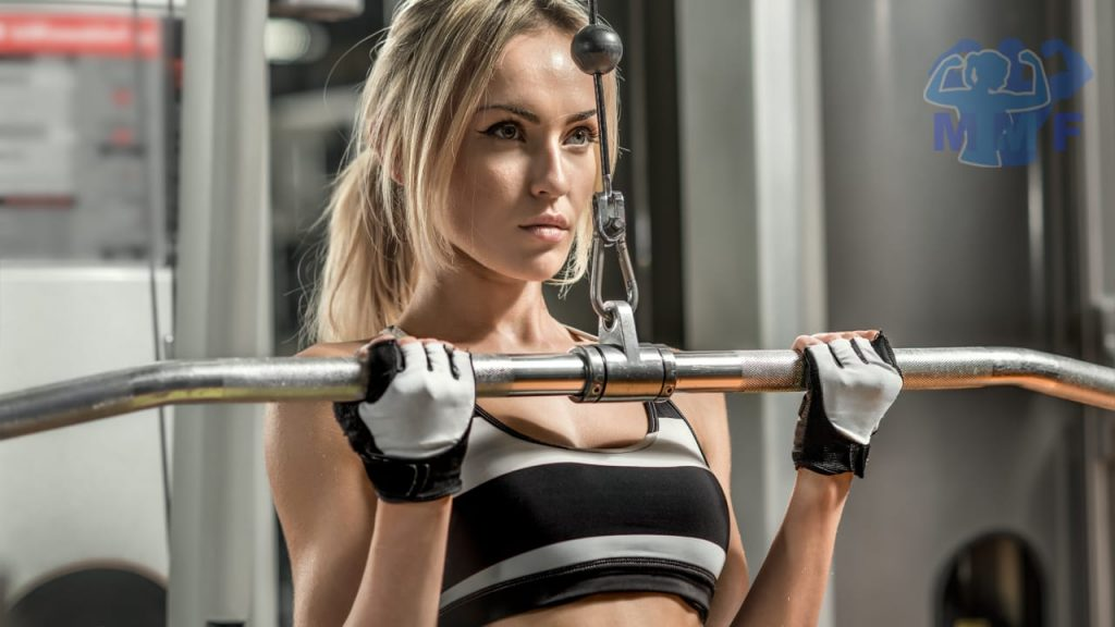 Fit blonde woman performing supinated lat pulldown.