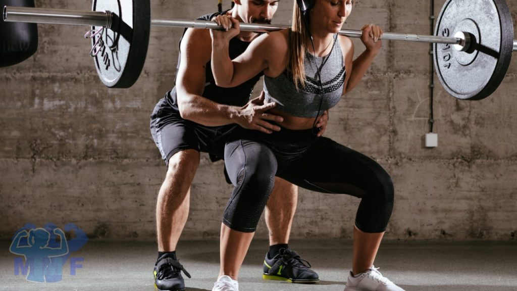 Man spotting a fit woman squatting for the genuine benefits of weightlifting For Your health at any age.