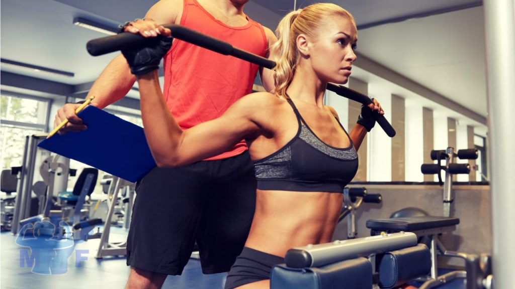 Fit woman with personal trainer doing one of the worst weightlifting exercises behind the back lat pulldowns.