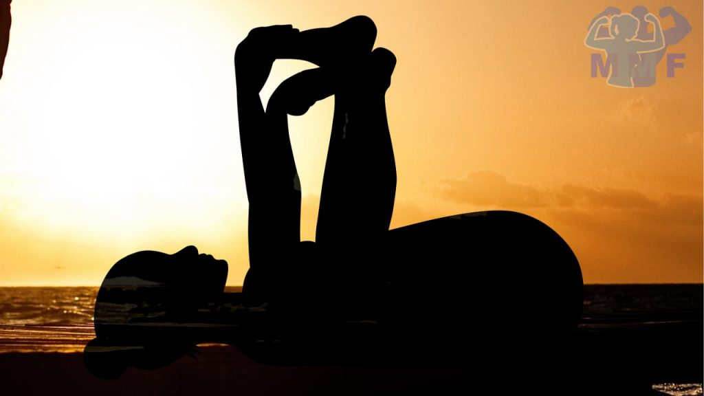 Woman silhouette performing happy baby at sunset doing Yin Yoga Benefits of Restorative Yoga.